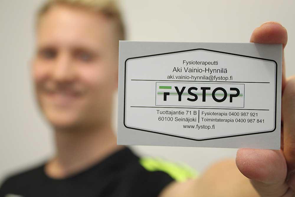Aki Vainio-Hynnilä näyttää käyntikorttia kameralle