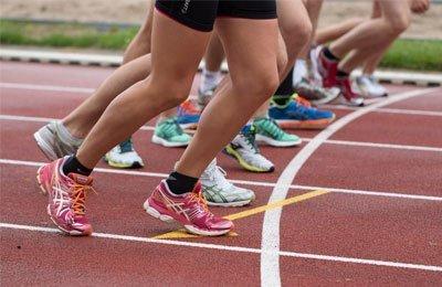 Juoksijoiden jalkoja lähtöviivalla